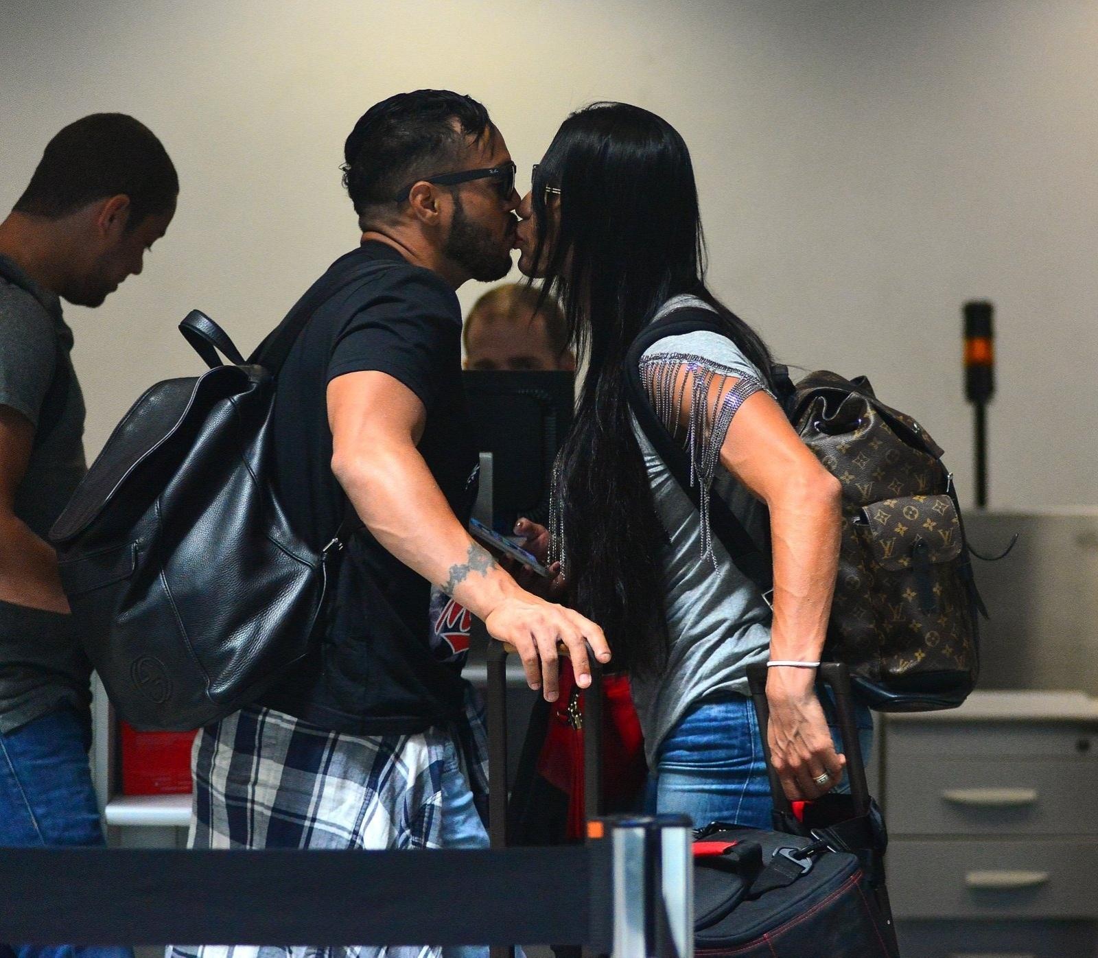 29.set.2015 - O cantor Belo e sua mulher, a dançarina Gracyanne Barbosa, trocaram beijos antes de embarcarem no aeroporto Santos Dumont, no Rio de Janeiro. O casal deu um selinho enquanto aguardava a fila do check-in.