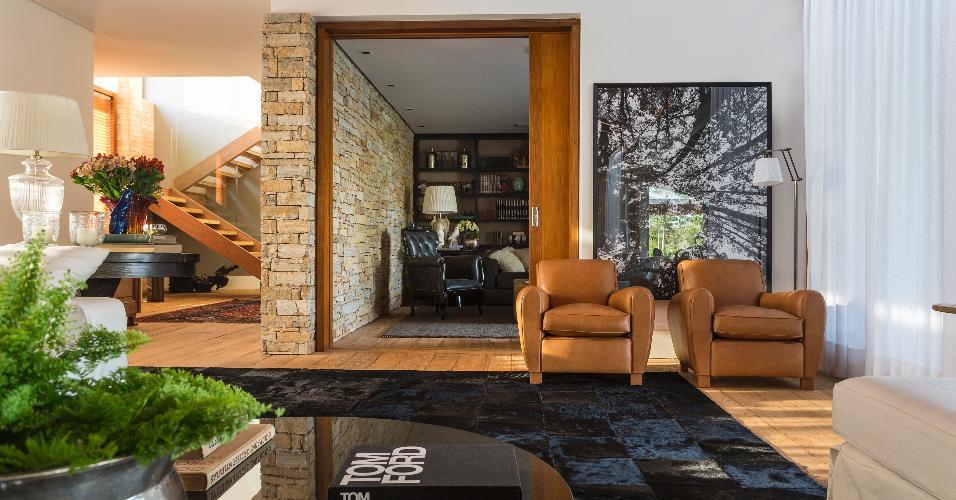 Na casa de campo no interior de São Paulo, a sala de TV fica ao lado do estar. A parede de pedra e o uso de madeira e couro no mobiliário seguem o estilo rústico adotado pelo arquiteto Maurício Karam. Ao fundo, as escadas dão acesso a duas suítes e ao terraço