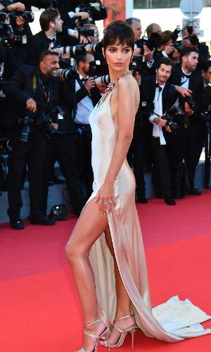 Ao chegar em Cannes, a atriz e modelo Emily Ratajkowski deixa as pernas à mostra em um vestido com enorme fenda