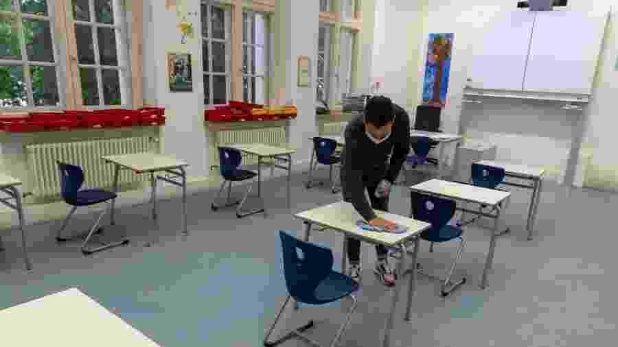 Professor desinfeta mesas da sala de aula para receber alunos na volta às aulas em Munique, na Alamanha - Getty Images