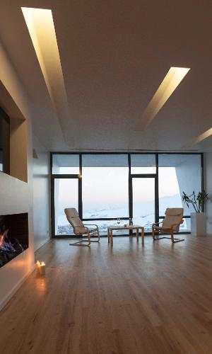 O 'living' da casa Mosha, em Teerã (Irã), assinada pelo escritório New Wave Architecture, tem esquadrias que vão do chão ao teto para propiciar a apreciação da paisagem. O piso em madeira clara aquece o ambiente e a iluminação é indireta e realizada por rasgos no teto, preenchidos por lâmpadas amareladas