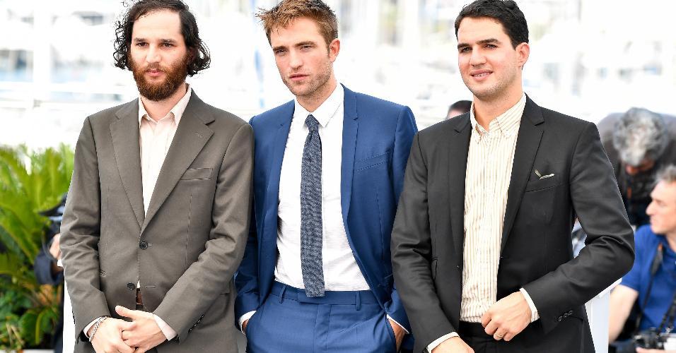 Os diretores Josh Safdie, Benny Safdie com o ator Robert Pattinson em Cannes, na França