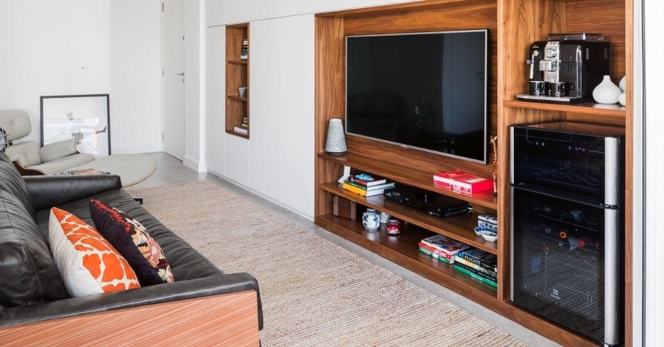 Na sala de estar, a parede que antes era ocupada pela bancada da cozinha, hoje abriga um armário-curinga, que reúne guarda-roupa, rouparia, estante e espaço para o armazenamento de produtos de limpeza, aspirador de pó e, ainda, home theater e apoio para a cafeteira e adega. O móvel foi executado pela Marcenaria Simão e o projeto de reforma é da arquiteta Marcela Madureira