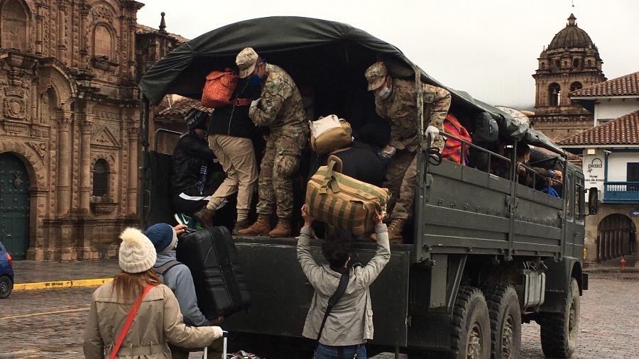 Turistas brasileiros sobem em caminhões do exército para seguir ao aeroporto internacional de Cusco - Luciana Sarmento/UOL