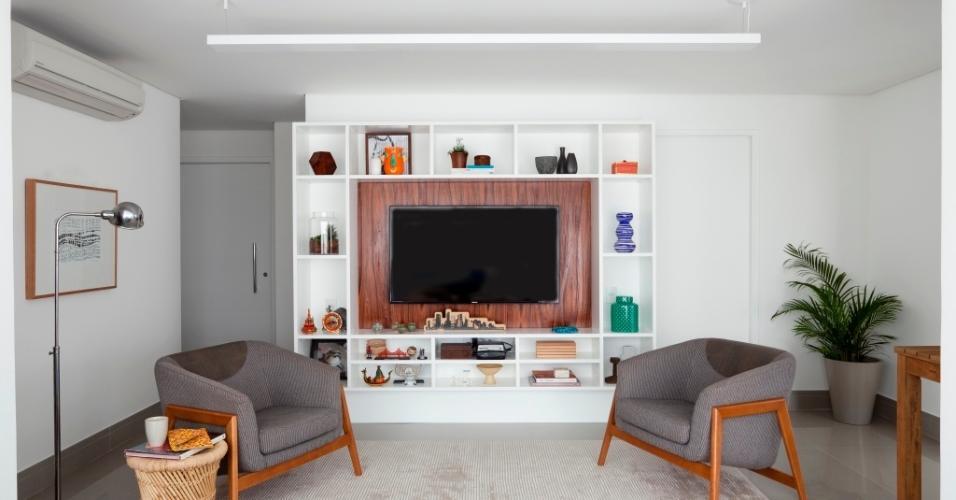Nuanças de cinza predominam no mobiliário do estar do apartamento Alto do Ipiranga, reformado pelo escritório Iná Arquitetura. As poltronas (Espaço Til) dialogam com o piso e com o tapete (Tabriz). Para quebrar a frieza dada pelas cores base (cinza e branco), a mesa lateral de vime (Espaço Til) e o painel da TV, em pau-ferro, se alinham à luminária de piso (Etna) e aos quadros (Fast Frame)