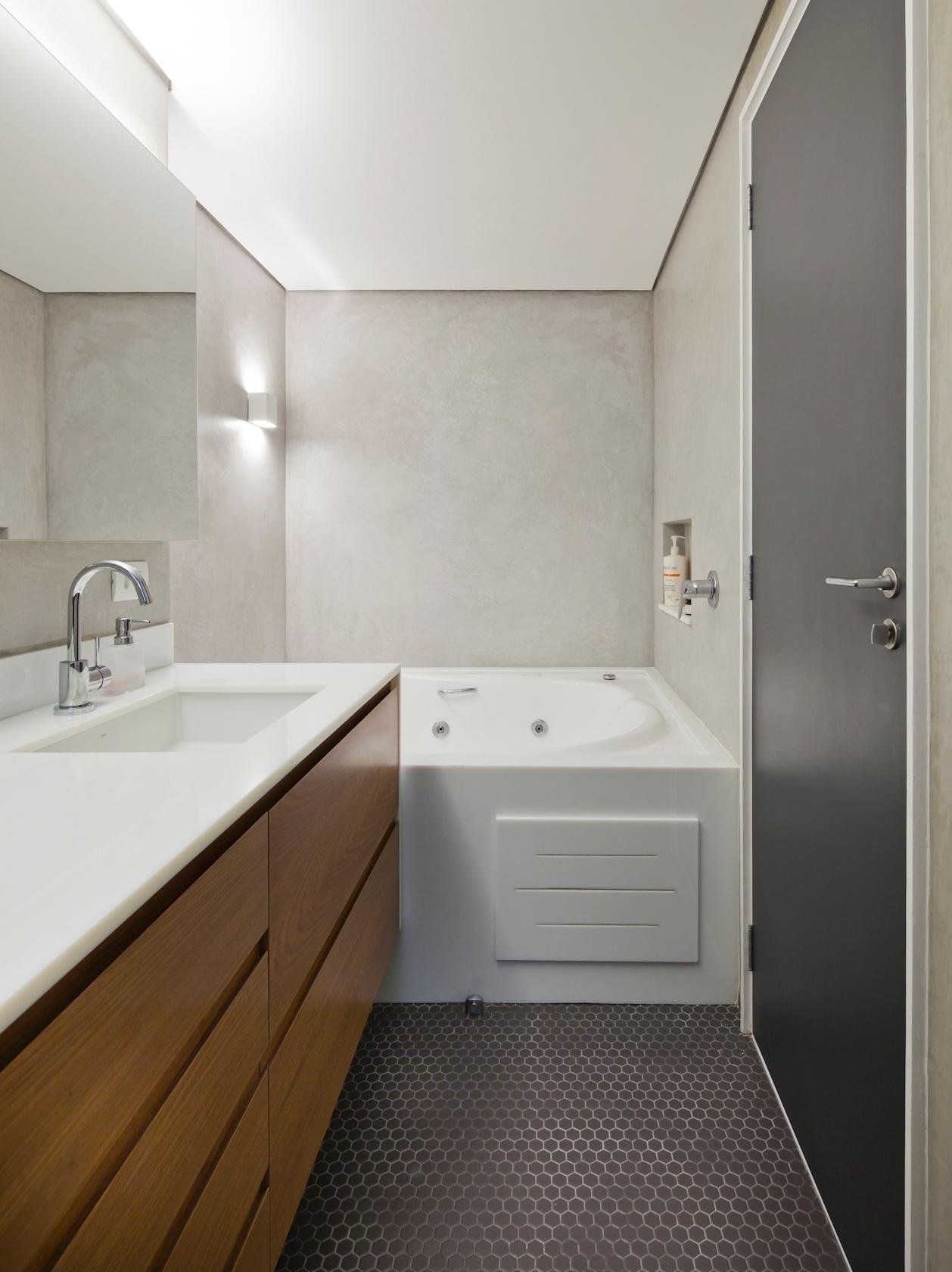 O banheiro de casal do apartamento de 160 m2, no Paraíso, zona sul de São Paulo, tem box de um lado e banheira de hidromassagem do outro, ligados por piso de pastilha hexagonal cinza. A bancada conta com gabinete em madeira freijó e tampo de massa sintética de vidro, com duas cubas. O projeto é definido por Renato Dalla Marta, do AUM Arquitetos
