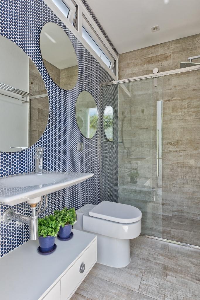 O banheiro que serve a piscina recebeu pastilhas hexagonais azuis (Portobello) na parede que apoia os espelhos. O piso e as demais paredes são revestidas com cerâmica que imita madeira. Janelas altas basculantes garantem privacidade aos usuários do ambiente da casa Alphaville, com projeto de Carla Kiss, na região metropolitana de Curitiba (PR)