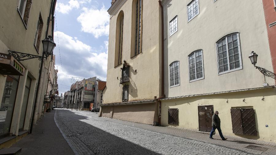 """Homem com máscara facial atravessa a rua quase vazia em Vilnius, Lituânia, durante """"lockdown"""" - Paulius Peleckis/Anadolu Agency via Getty Images"""