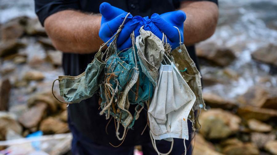Máscaras recolhidas em uma praia de Hong Kong em maio - Anthony Wallace/AFP