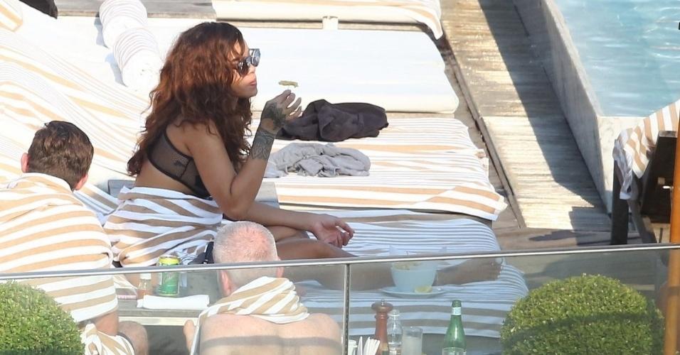 28.set.2015 - Rihanna é flagrada pegando sol e comendo um petisco na piscina do hotel Fasano, em Ipanema, zona sul do Rio de Janeiro