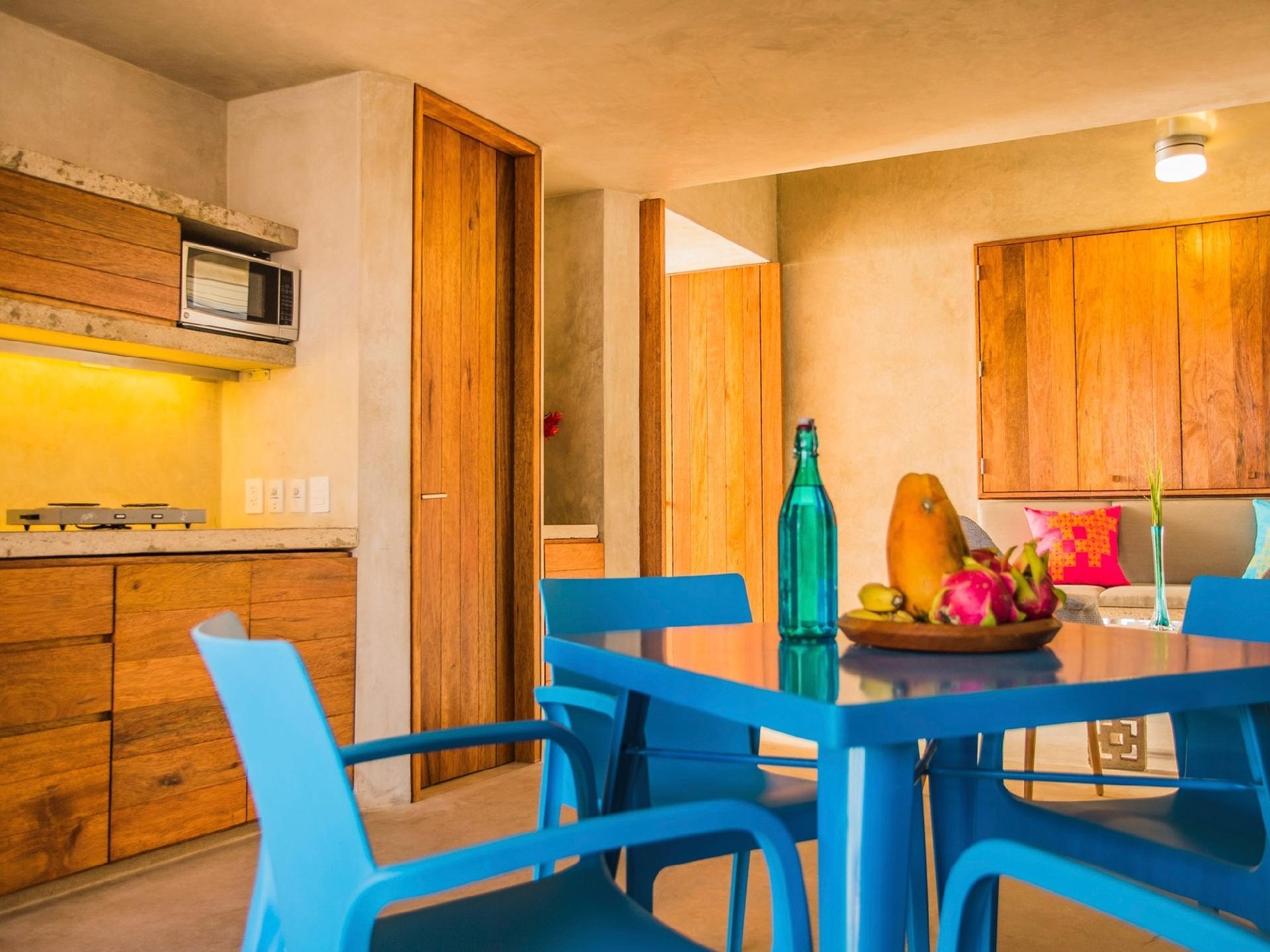 No espaço de jantar, as cadeiras (Offiho Mobili) são de polipropileno e resistentes a umidade, maresia e raios ultravioletas. Também em azul, a mesa Tolix (Innrent) tem estrutura metálica. O projeto desenhado pelo escritório Taco - Taller de Arquitectura Contextual para a casa Gabriela priorizou espaços pequenos e integrados. Ao fundo, a porta dá acesso ao banheiro