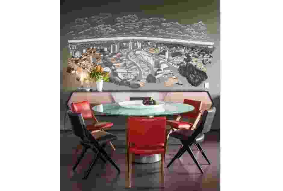 Neste projeto, dos arquitetos Alice Martins e Flávio Butti, o fundo da sala de jantar recebeu uma pintura que representa a vista que os moradores teriam se não houvesse uma parede ali. Criado pelo artista e fotógrafo Ricardo Migliorini, o desenho, além de adicionar profundidade ao ambiente, serve de inspiração para quem não pode modificar a estrutura do imóvel para abrir uma janela - Ricardo Migliorini/ Divulgação