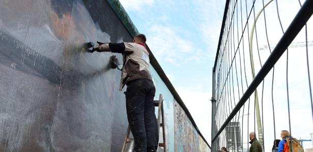 """5.nov.2015 - Pichação é removida atrás de uma cerca temporária na parte do Muro de Berlim conhecida como """"East Side Gallery"""". A área ganhará uma barreira fixa - John MacDougall/AFP"""