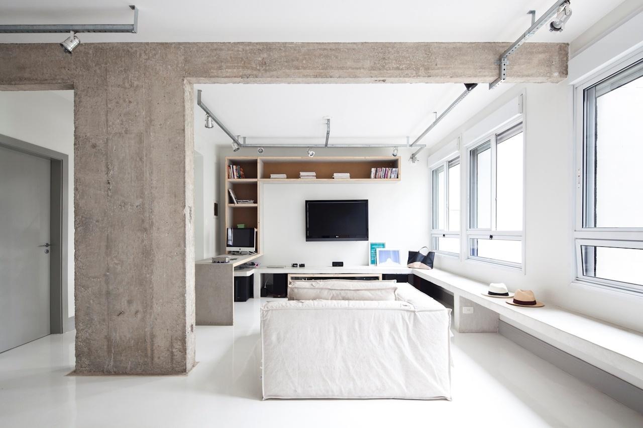 O sofá creme da Carbono Design antecede a sala de TV e o canto-escritório (à esq.). À direita, um grande banco de concreto  percorre uma das paredes do apê Perdizes e pode ser usado como assento ou como apoio para objetos de decoração. A marcenaria que sustenta a TV é formada por um sanduíche de placas de fibrocimento e folhas de madeira. Os interiores são do SuperLimão Studio
