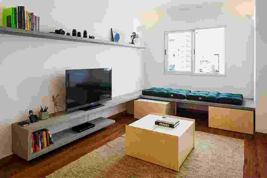 No estar, o banco de concreto armado e moldado in loco funciona também como rack para a TV e para a exposição de objetos. Sob essa plataforma ficam acomodados caixas em marcenaria que servem como área de armazenamento e podem ser adotados como mesa de centro (foto) ou assento extra. Uma estante também em concreto otimiza o espaço, ganhando mais espaço para livros e coleções. O projeto de reforma do apartamento em São Paulo (SP) é assinado pelo Grupo Garoa Arquitetos - Rafaella Netto/ Divulgação