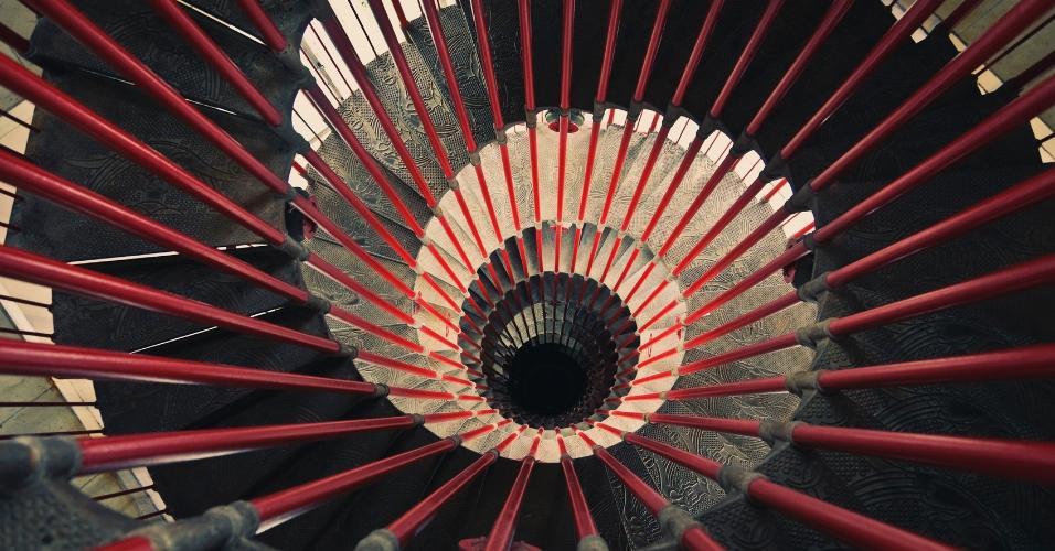 Escadas em formato caracol são chiques, ainda mais quando os degraus ganharam aplicações em alto-relevo, como neste exemplo. O ar medieval é quebrado pelo guarda-corpo de metal tingido de vermelho e que acompanha toda a altura das curvas espiraladas