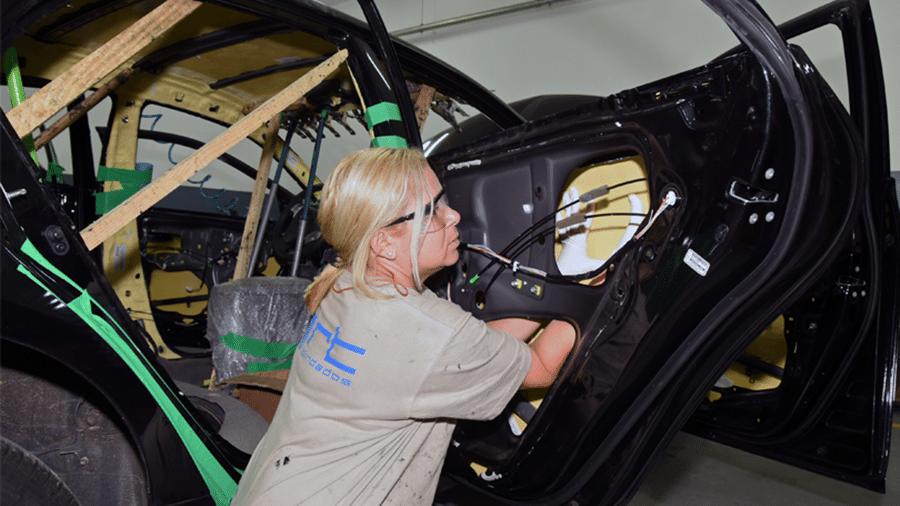 Funcionária de blindadora aplica manta de proteção balística na porta traseira de um automóvel - Murilo Góes/UOL