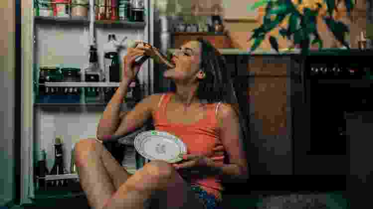 Mulher comendo pizza engordar na quarentena - domoyega/Getty Images/iStockphoto - domoyega/Getty Images/iStockphoto