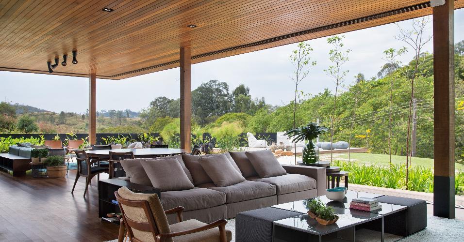 Ao abrir as portas de correr, que circundam as salas, o living da casa de campo projetada pelo arquiteto Otto Felix se conecta à paisagem. O estar e a área de jantar foram decorados com peças requintadas. São destaques o sofá Groundpiece, da Flexform, e a mesa de centro Area, da B&B Italia