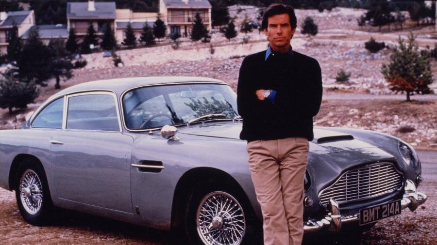 """Pierce Brosnan posa na frente do Aston Martin usado em """"007 Contra GoldenEye"""" - Reprodução"""