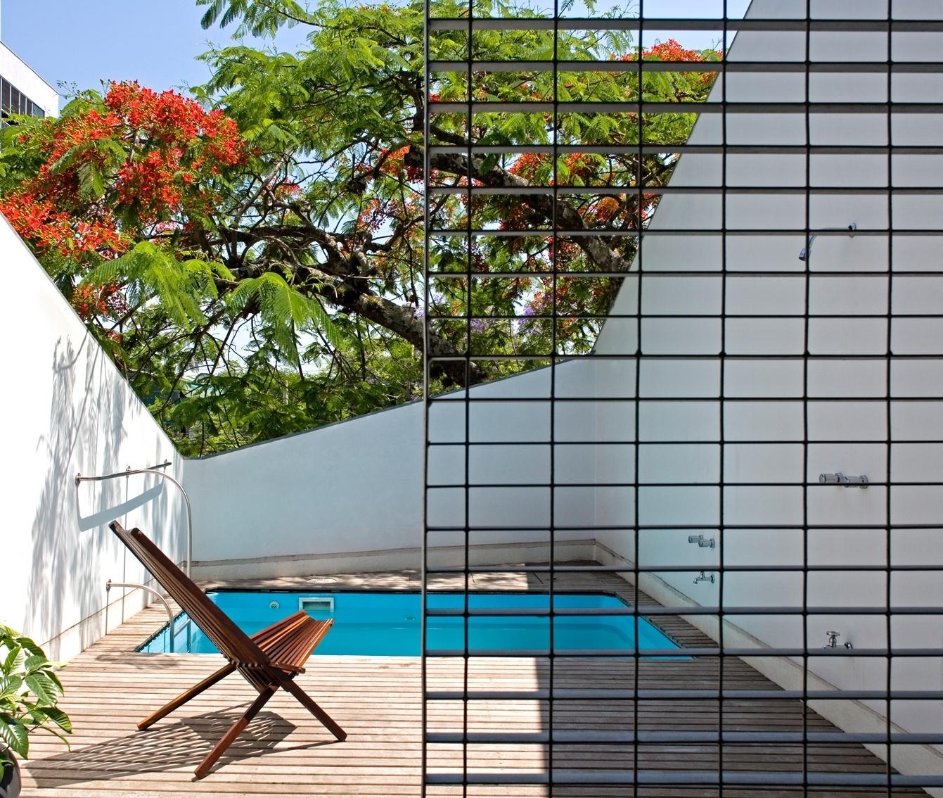 A piscina da Slice House é um bloco flutuante: a superfície da água está no mesmo nível do piso do pavimento superior e a parede com que o deck faz contato (alvenaria, acima do nível da água) abriga um ambiente para hóspedes. Abaixo do nível da água, a parede da piscina é de vidro estrutural e funciona como janela para a sala de estar. A casa em Porto Alegre (RS) tem projeto do escritório Procter-Rihl