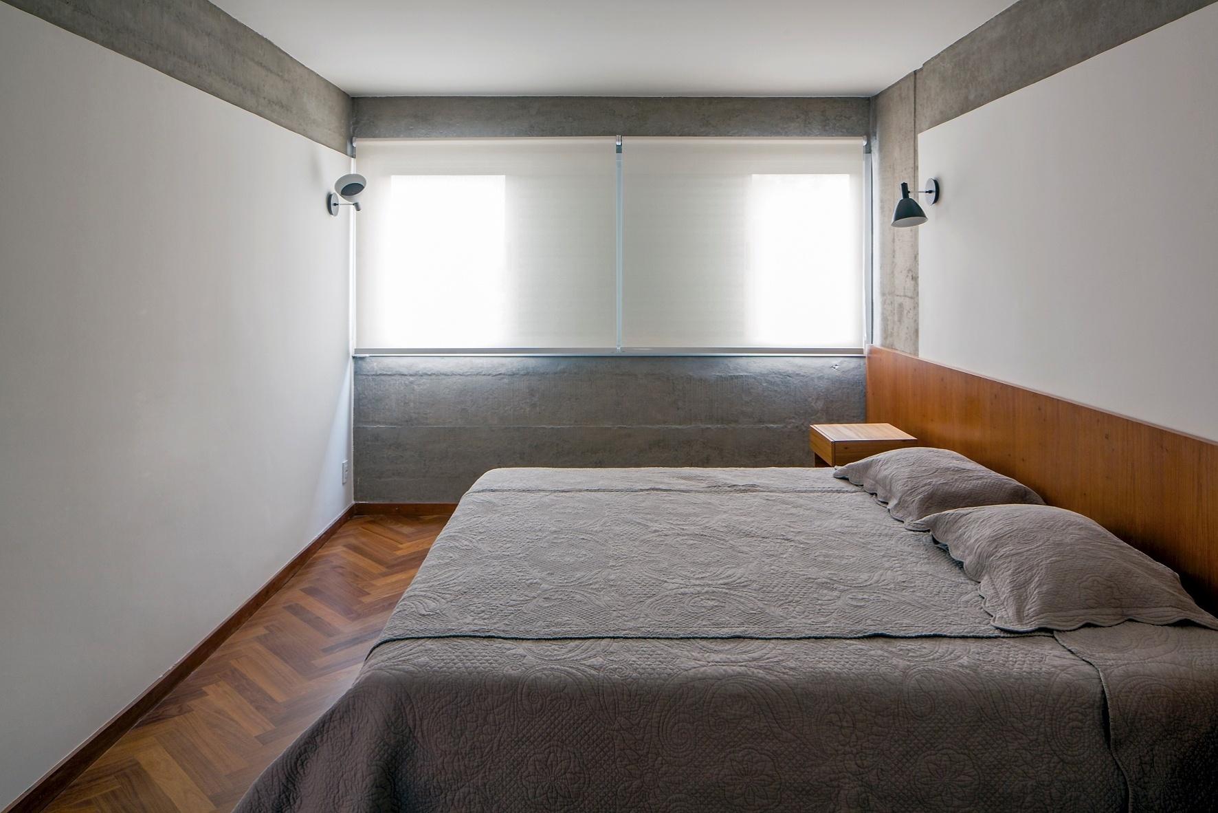 A principal mudança na planta do Apartamento FT está na área íntima: dois dormitórios se transformaram em apenas um, mais espaçoso e com closet. Nele, os elementos estruturais também ficam expostos e, como na área social, não há iluminação direta central: a luz das arandelas são refletidas nas paredes brancas. A reforma foi projetada pelo escritório Pascali Semerdjian Arquitetos