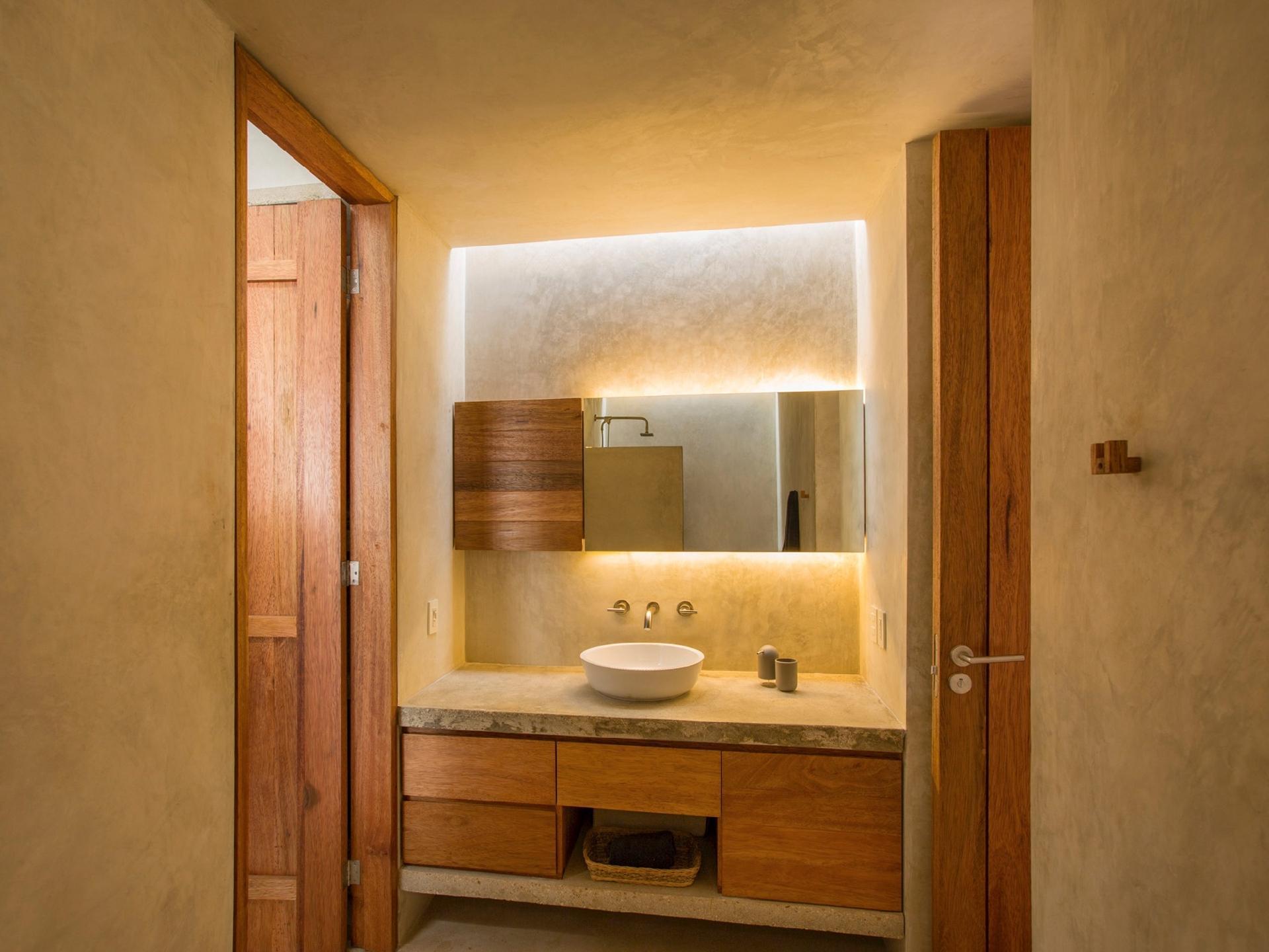 Além da iluminação embutida atrás do espelho, o banheiro conta com uma abertura no forro (claraboia). A porta à esquerda dá acesso direto para o único dormitório da casa Gabriela. A segunda abertura está voltada ao living, assim o ambiente é uma espécie de passagem. O projeto de arquitetura é do Taco Taller de Arquitectura Contextual