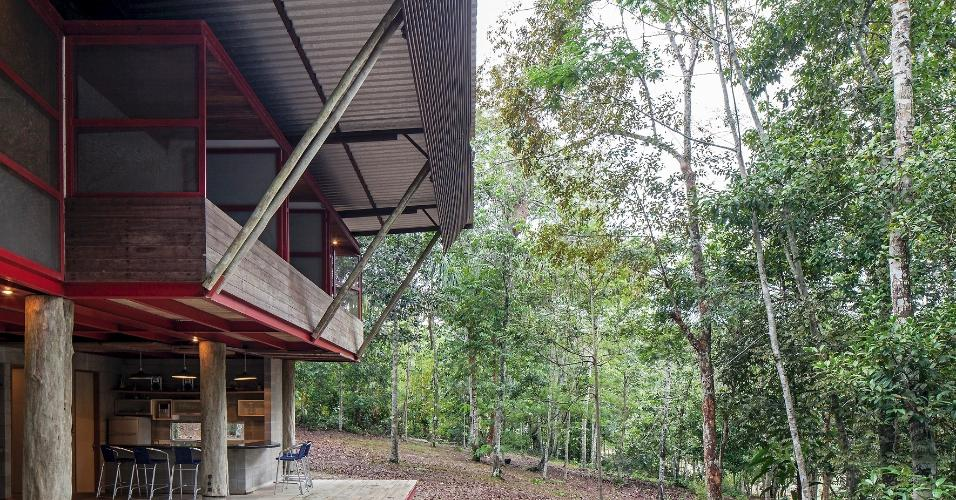 A cobertura de telhas de alumínio alia o baixo peso ao aproveitamento da sombra fresca dada pelas folhas das árvores. Uma grade metálica inclinada desce da cobertura: é um brise, que funciona como