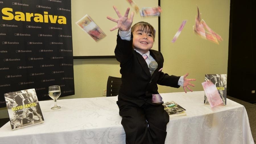 """Ana Clara, vestida de """"Silvinha Santos"""", joga dinheiro para o alto durante o lançamento do livro """"Silvio Santos - A Trajetória do Mito"""" - Francisco Cepeda/AgNews"""