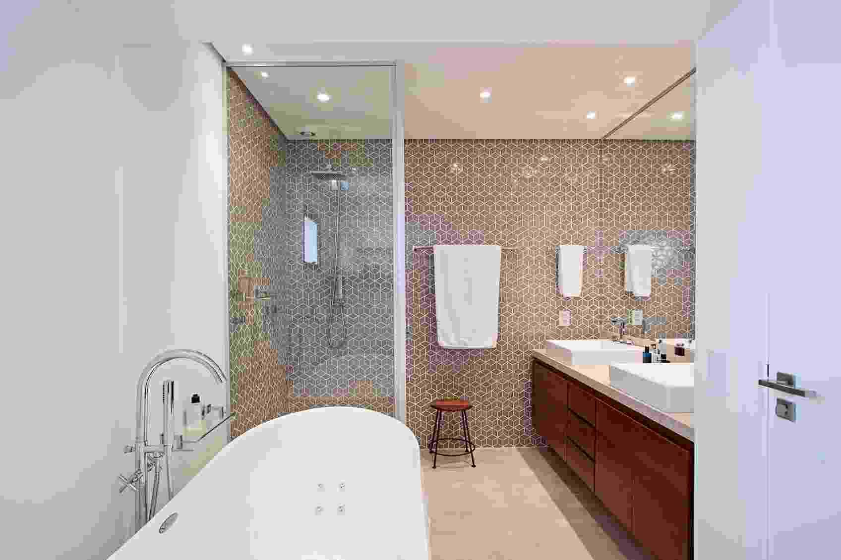 Na reforma comandada pela Korman Arquitetos, o quarto de empregada e o antigo banheiro foram integrados para criar essa generosa sala de banho. O piso tem porcelanato com visual de cimento queimado e as paredes receberam mosaico cerâmico (Portobello), que virou a atração do espaço. Destaque para a banheira do tipo freestanding (Spas Versati), que fica separada da área do boxe - Gui Morelli/Divulgação