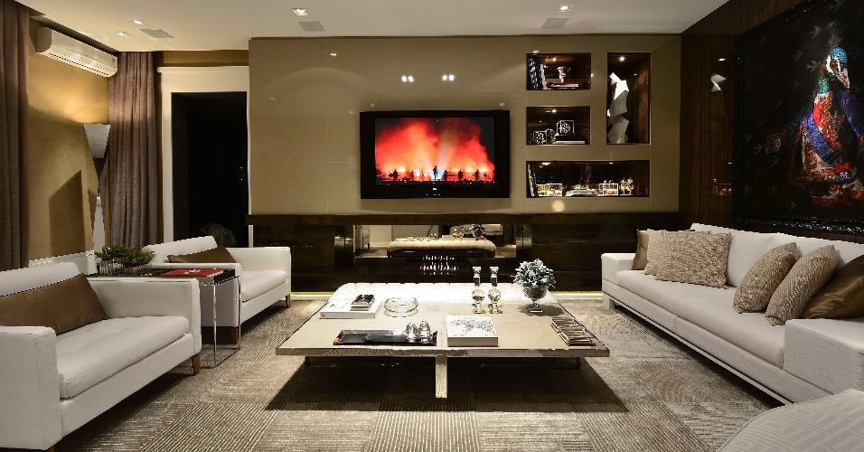Francisco Humberto Franck é o responsável pelos 36 m² do living FHF 40. Inspirado nos anos 1970, o espaço é decorado com móveis claros, baixos e de linhas retas. As paredes receberam acabamentos em alto brilho e a superfície que sustenta a TV foi recortada e abriga nichos (à dir.)