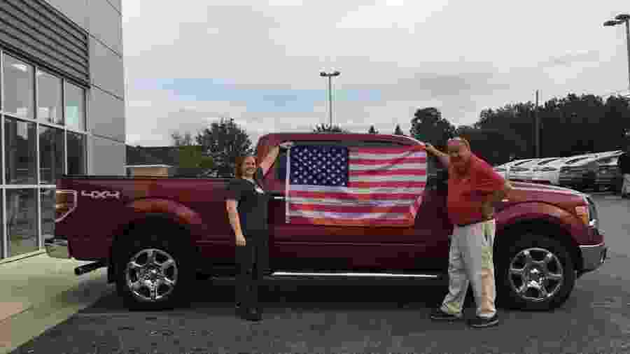 Cliente de concessionária da Ford posa com bandeira dos EUA após comprar carro - Divulgação