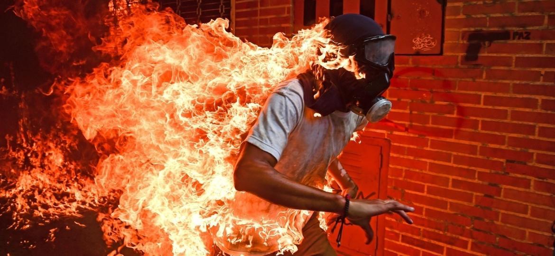 Estudante Víctor Salazar corre  após a explosão do tanque de gasolina de uma moto durante protesto em Caracas - Ronaldo Schemidt/AFP)