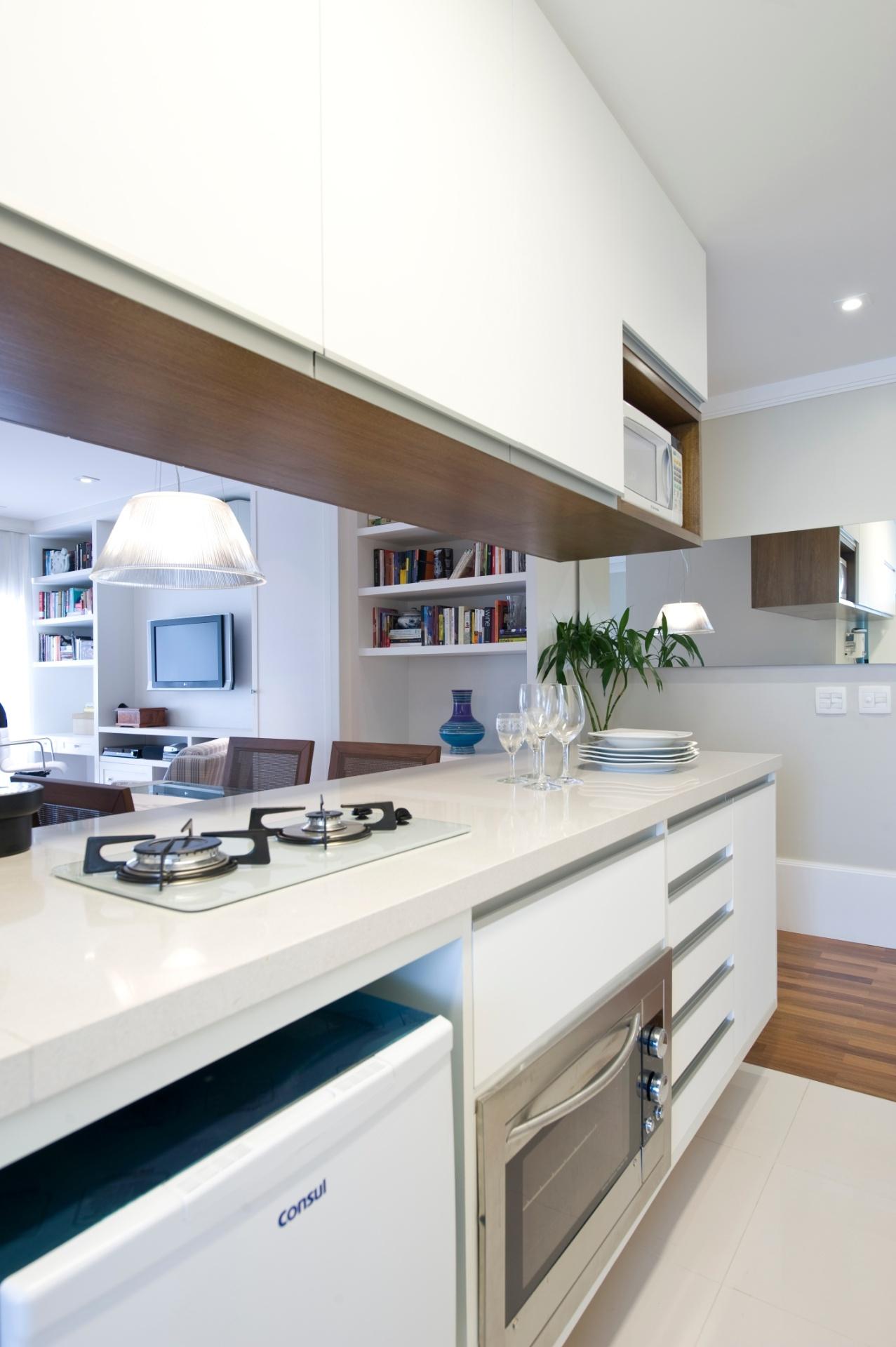 A bancada branca desta cozinha integrada tem eletrodomésticos embutidos e gavetas para a organização dos utensílios. Para oferecer mais espaço para o armazenamento, o escritório In House projetou um armário superior, branco também, mas com detalhes em madeira escura