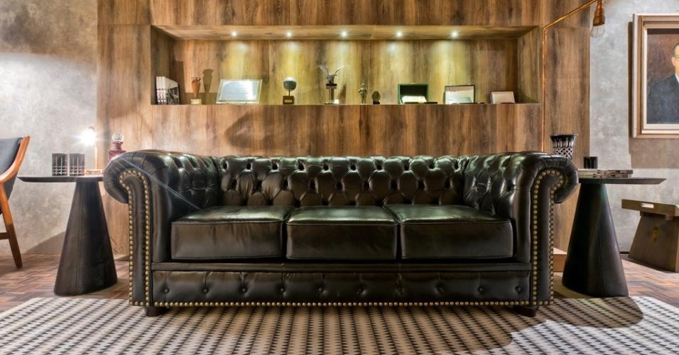 A Sala de Troféus, com 45,9 m², de Luiz Mangué, exibe um tapete tricolor com listras e zigue-zagues combinado com móveis escuros. Um exemplo é o sofá ricamente trabalhado em couro, com detalhes em tachas douradas e acabamento capitonê