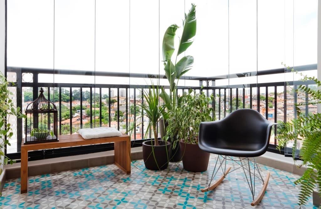 Na varanda do apê Cátia, praticamente tudo é novo: o ladrilho hidráulico, a cadeira Eames Wood de balanço e o banco de madeira Tok&Stok. Apenas o fechamento em vidro já existia antes do projeto de reforma executado pelo escritório Iná Arquitetura