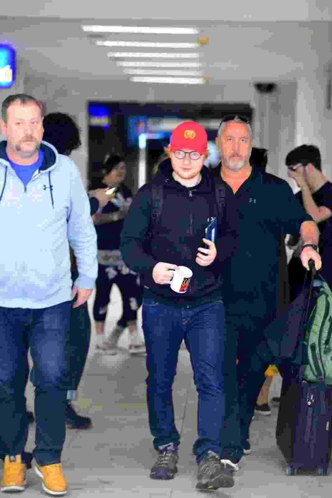 De boné vermelho, Ed Sheeran desembarca no aeroporto Santos Dumont, no Rio. O cantor se apresenta nesta quinta-feira na cidade - William Oda /AgNews