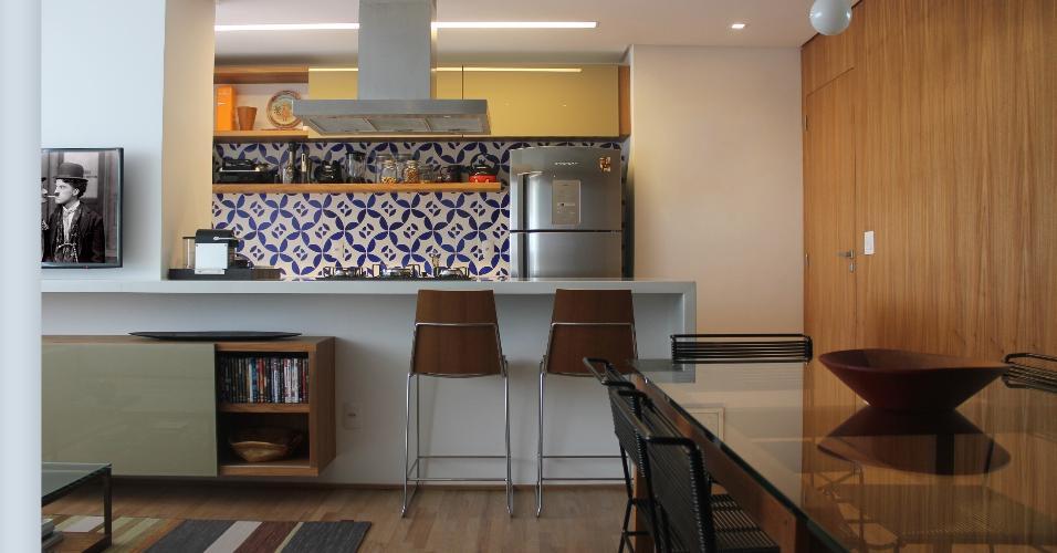 5,60 m². Ao eliminar a parede entre a cozinha e a sala, o arquiteto Felipe Rassini trouxe amplitude aos espaços. Sob o armário instalado rente ao reto, ele bolou uma prateleira que deixa condimentos, livros de receitas e outros itens sempre a mão. O painel de azulejos é o elemento mais elogiado por quem chega.