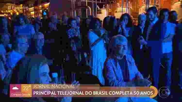 Tulio Gadelha aparece no canto, à direita, mexendo no celular, durante a festa de 50 anos do Jornal Nacional - Reprodução/Globo - Reprodução/Globo