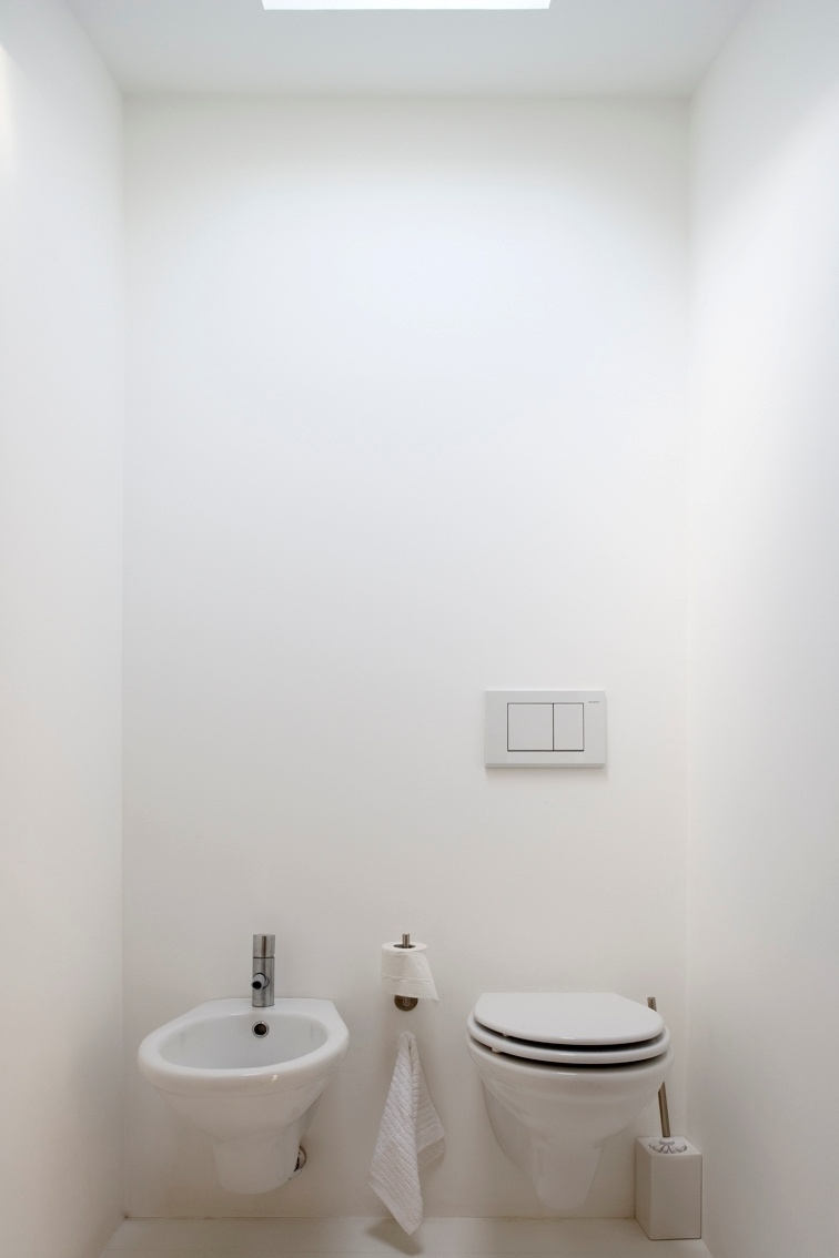 A ducha e as instalações sanitárias (foto) ficam no piso superior do antigo sótão, junto às empenas laterais, que recebem luz natural via lanternins (aberturas), no cume da Casa Maria Borges, em Lisboa, Portugal. O projeto de reforma é de João Favila Menezes, do Atelier Bugio