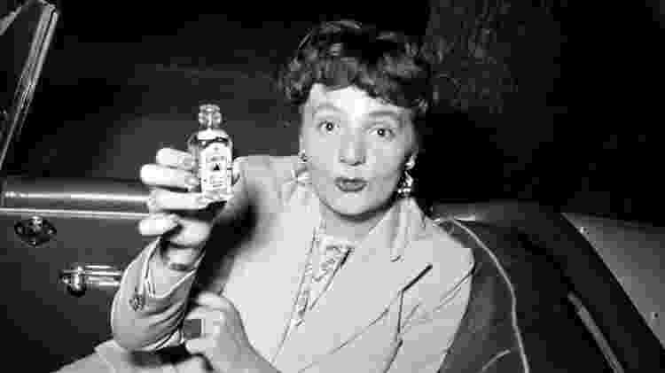 Mulher mostra pequena garrafa de gim em foto de 1960 - Corbis via Getty Images - Corbis via Getty Images
