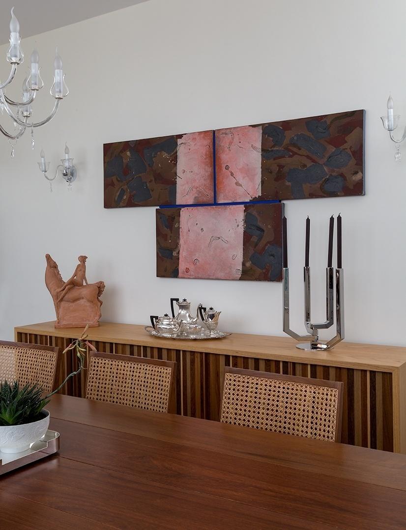 Encontrar o lugar certo para um quadro também é sinônimo de estudo das proporções. A pintura marrom e rosa por ser mais alongada pôde ser pendurada sobre o bufê, pois acompanhava seu comprimento. Além disso, não