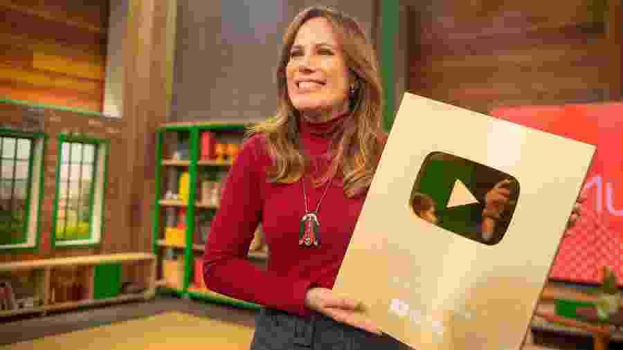 """Regina Volpato, apresentadora do """"Mulheres"""", com a placa comemorativo de um milhão de inscritos - Mariana Cavalcanti"""