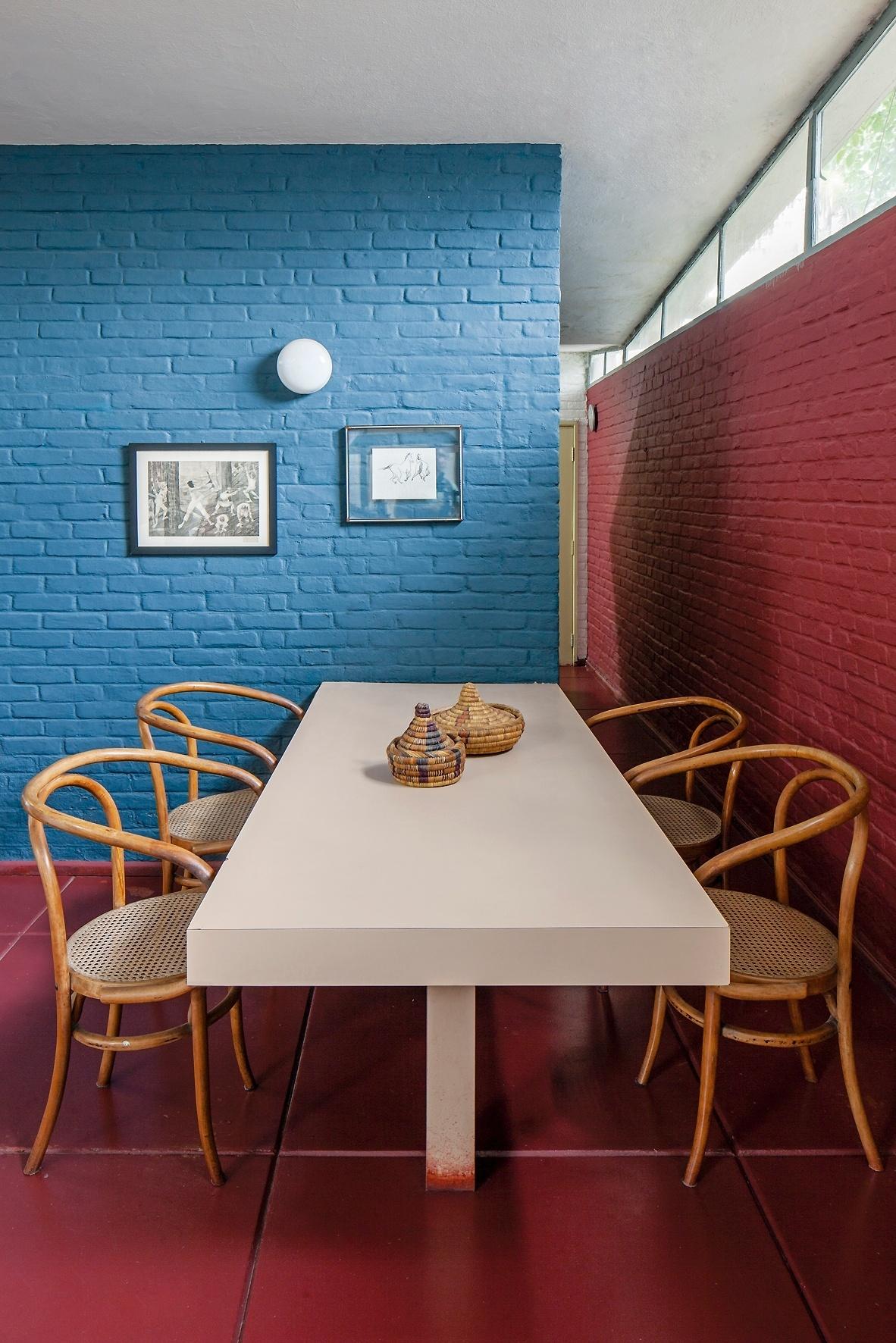 Os tijolos das paredes foram deixados à vista e pintados, ora de azul, ora de vermelho, em harmonia com o piso. A mesa de refeições é servida pelas cadeiras Thonet, em voga na época da construção (1949). A passagem lateral (à dir.) dá acesso à cozinha da Casa do Arquiteto, projetada por João Batista Vilanova Artigas (1915-1985)