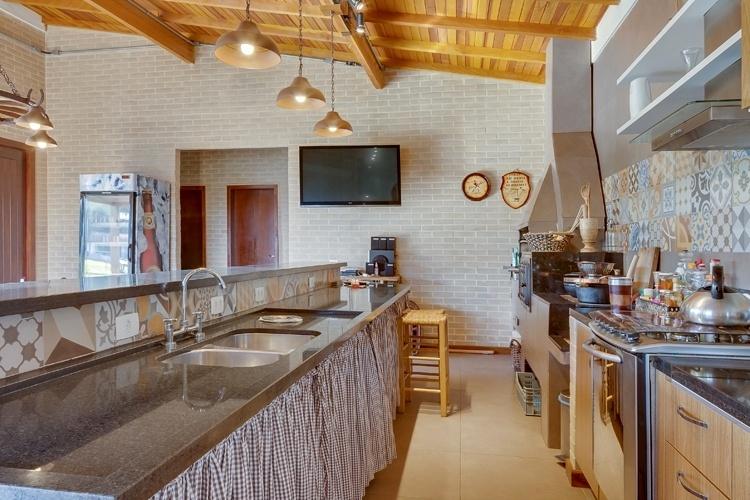 O espaço gourmet desta residência em Araucária (PR), projetado pela arquiteta Juliana Lahóz, apresenta piso em porcelanato e forro de madeira, além dos pendentes em estilo