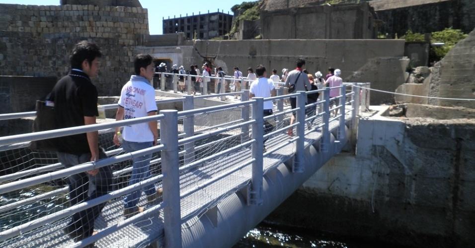 Turistas chegam à ilha conhecida como Gunkanjima, no sul do Japão