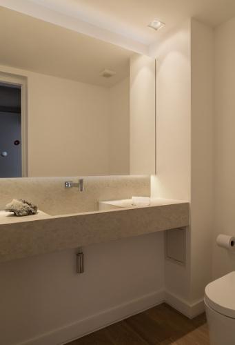 O lavabo que fica logo na entrada do apê reformado pelo arquiteto Giancarlo Rocco, em São Paulo, é monocromático e conta com um generoso espelho. O espaço fica detrás de uma porta