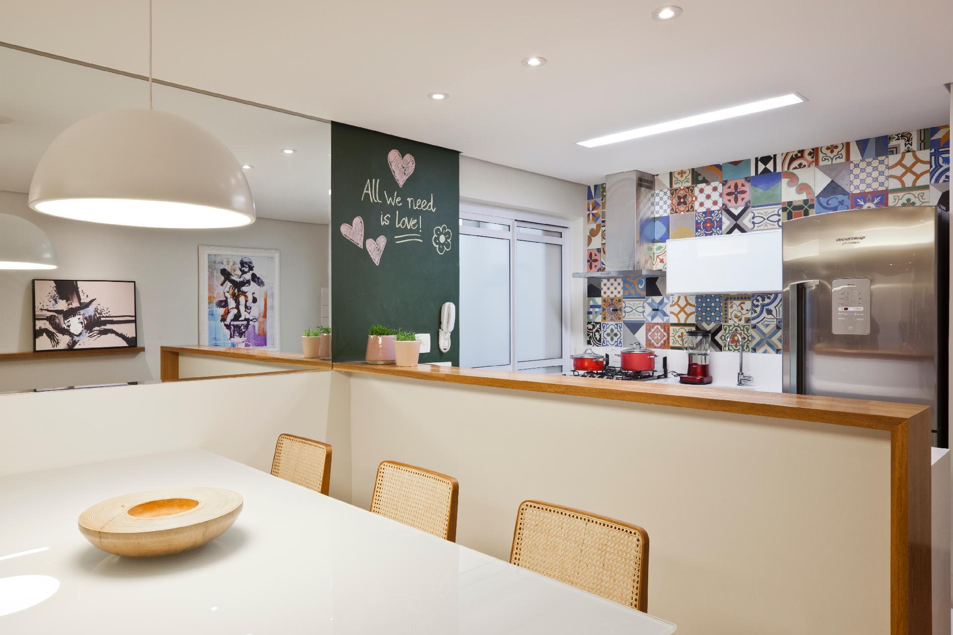 O apê feminino ganhou mais amplitude com a criação de uma cozinha americana e a instalação de um espeho junto à mesa de jantar. Os ladrilhos hidráulicos e a parede pintada com tinta de lousa dão um toque de jovialidade à decoração concebida para uma universitária. O projeto é assinado pelos arquitetos do escritório Conrado Ceravolo, em São Paulo