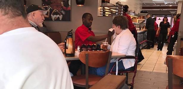 O garçom Joe Thomas alimenta Ma, a mulher tem uma doença que degenera o sistema nervoso