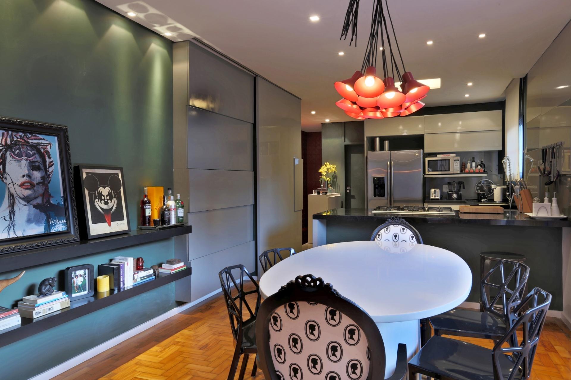 O jantar fica integrado à cozinha pela bancada de granito preto São Gabriel, que embute o cooktop. A parede com acabamento em tinta lousa verde (à esq.) é decorada com os quadros da Urban Arts. A casa Sumaré foi reformada pela arquiteta Renata Popolo e fica em São Paulo